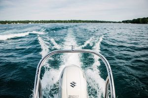 Arbor Financial Credit Union Boat Loans rear end of boat driving through lake with wake coming off of it